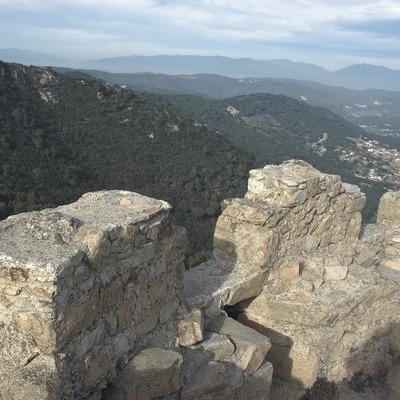 Restos arqueológicos del castillo de Burriac con la cordillera litoral al fondo.  (Turismo Verde S.L.)