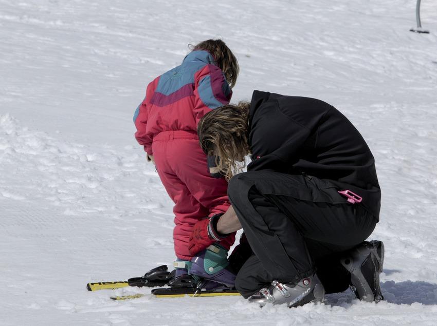 Инструктор надевает мальчику лыжи на горнолыжном курорте Вальтер-2000