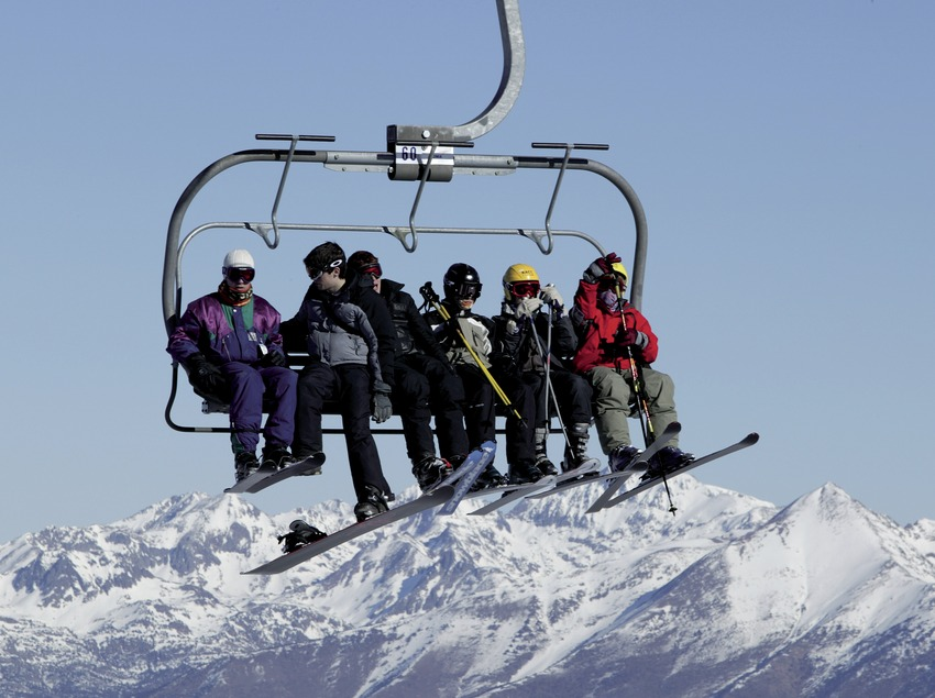 Skiers on a ski lift at the Port Ainé Ski Resort