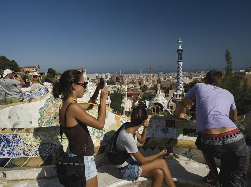 Turistes al banc ondulat del Park Güell amb la ciutat al fons  (Imagen M.A.S.)