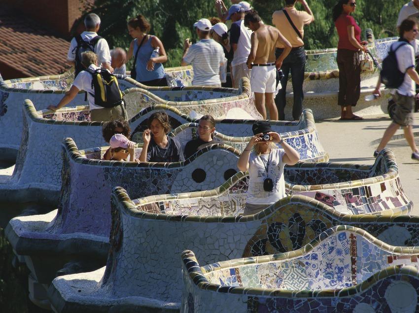 Туристы на волнистой скамье в Парке Гуэля