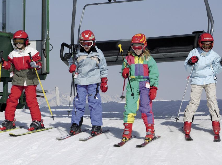 Skieurs enfants descendant d'un télésiège à la station de ski de La Molina (Nano Canas)