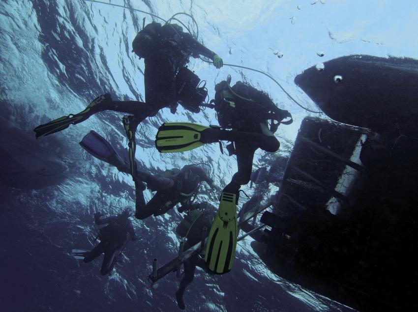 Taucher kehren nach einem Tauchgang zu den steilen Felswänden von Tamariu zum Boot zurück