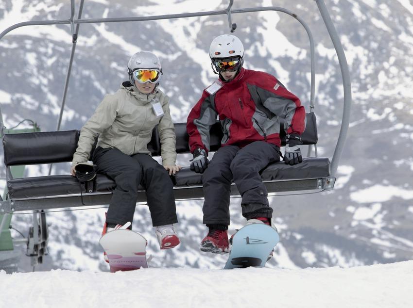 Esquiadors amb snowboard baixant d'un telecadira a l'estació Vall de Núria (Nano Canas)