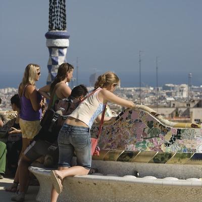 Turistas en el banco ondulado del Park Güell con la ciudad al fondo.  (Imagen M.A.S.)