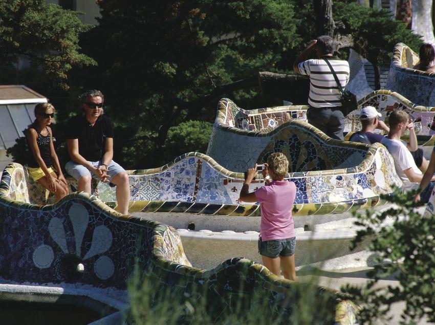Turistas en el banco ondulado del Park Güell
