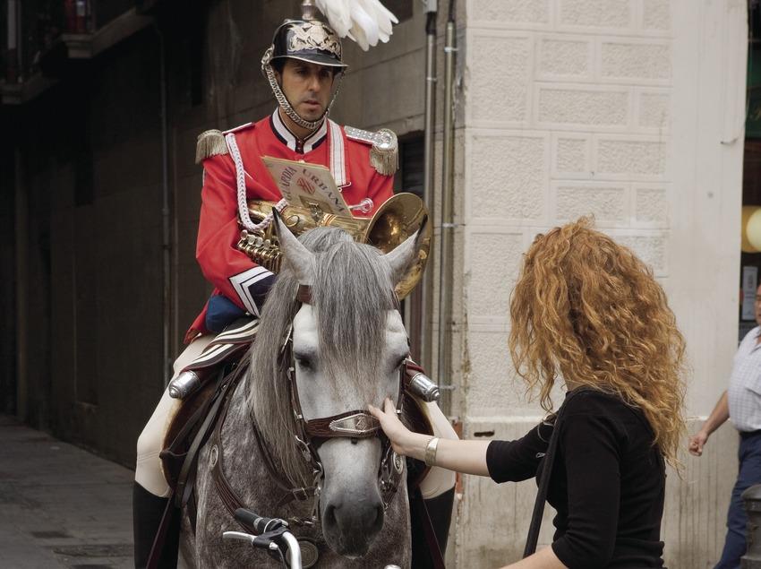 Chica en bici acariciando un caballo de la Guardia Urbana durante el pasacalles de las Fiestas de la Mercè (Oriol Llauradó)