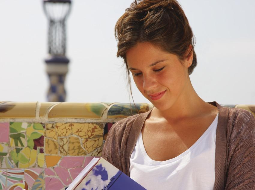 Chica leyendo en un banco ondulado del Park Güell.  (Lluís Carro)