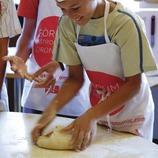 Niños haciendo pan en la Escola de Cuina de l'Empordà.  (Lluís Carro)