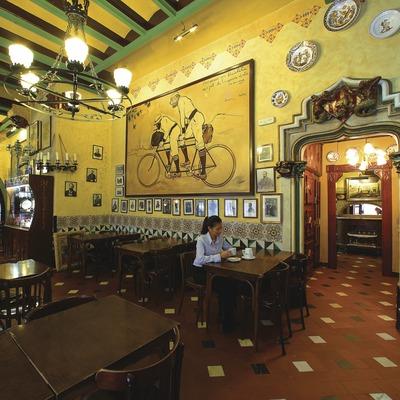 """Chica en el restaurante Els Quatre Gats. En la pared, reproducción de la obra """"Ramón Casas y Pere Romeu en un támden"""" (1897), de Ramón Casas.  (Lluís Carro)"""