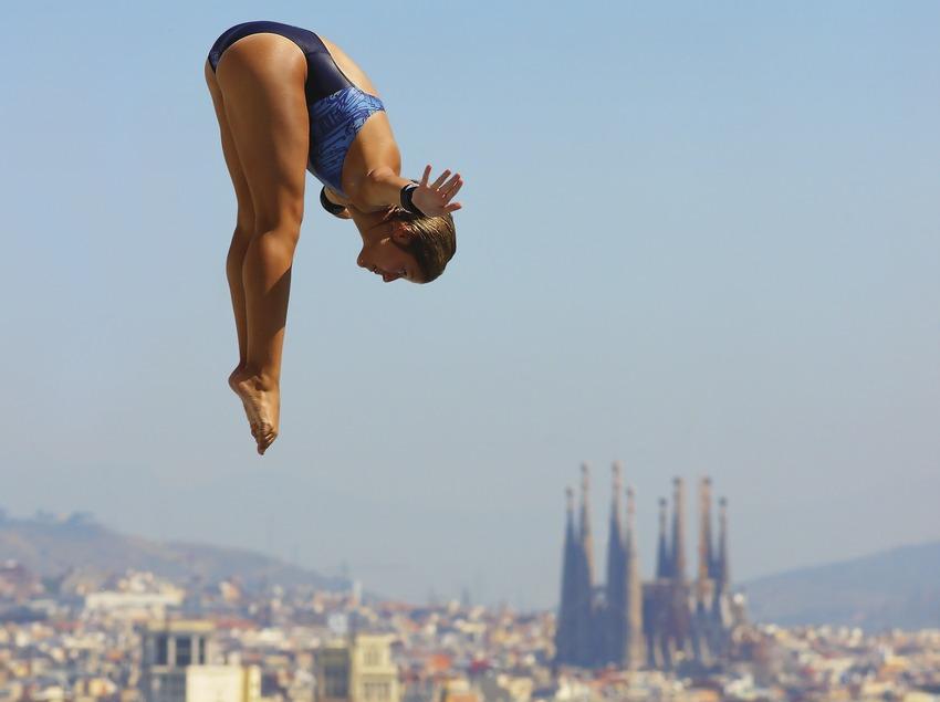 Salto de trampolín en las piscinas Picornell con la ciudad al fondo.  (Lluís Carro)