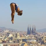 Salto de trampolín en las piscinas Picornell con la ciudad al fondo.