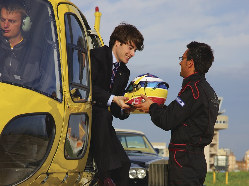 Ejecutivo recibe un casco de piloto de Fórmula de las manos de un técnico del Circuit de Catalunya.  (Lluís Carro)