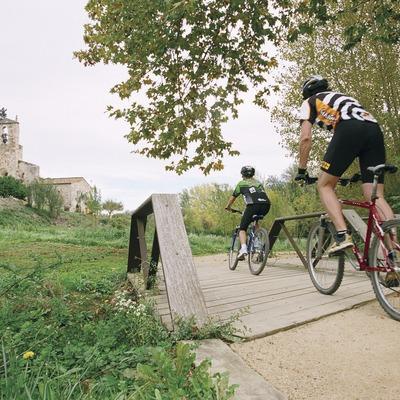 Ciclisme prop de l'església de Santa Maria de Porqueres   (Foto-tècnia fotògrafs)