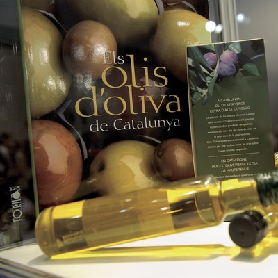Llibre Els olis d'oliva de Catalunya, amb el cartell fotogràfic i ampolles d'oli (Marc Castellet)