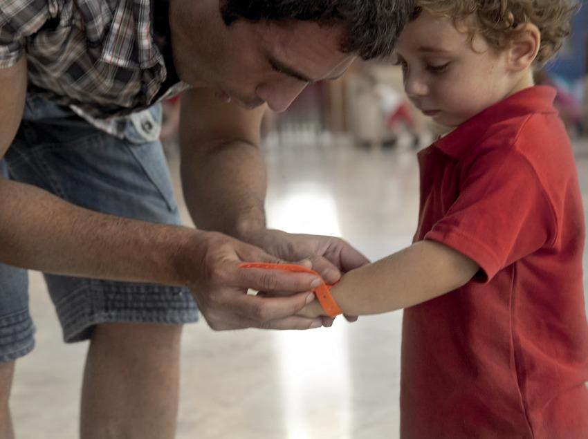 Pare posant una pulsera identificativa al seu fill a l'hotel Sol Costa Daurada (Cablepress)