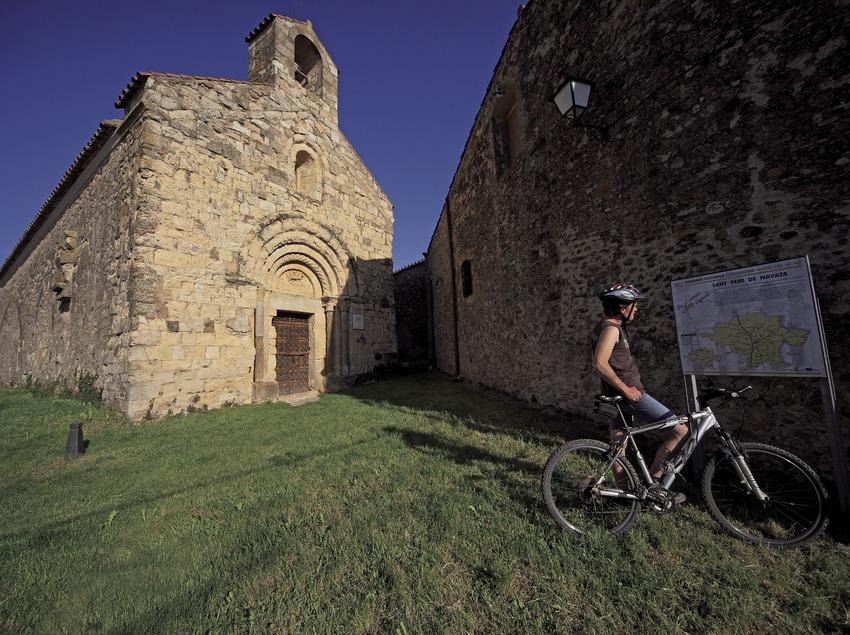 Consultando un plafón informativo de una ruta de BTT Salines-Bassegoda, ante la iglesia de Sant Pere de Navata