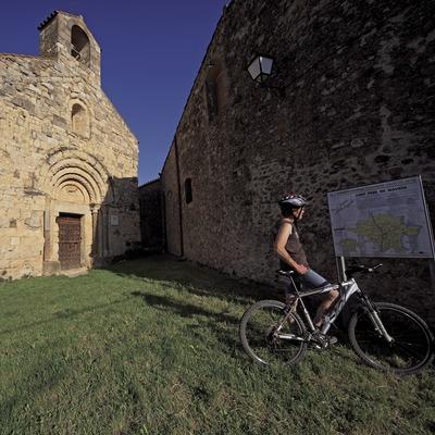 Consultant un plafó informatiu d'una ruta de BTT Salines-Bassegoda, davant de l'església de Sant Pere de Navata (Cablepress)