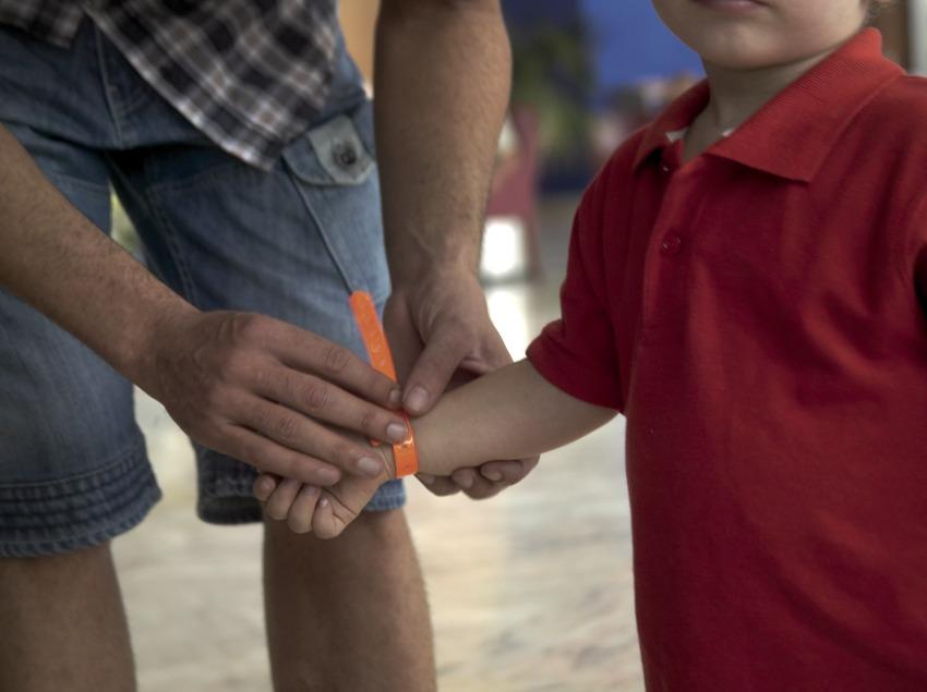 Detall d'un pare posant una pulsera identificativa al seu fill a l'hotel Sol Costa Daurada (Cablepress)