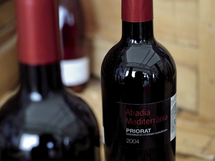 D.O.Q. Priorat, vi negre d'Abadia Mediterrània entre caixes de fusta i ampolles