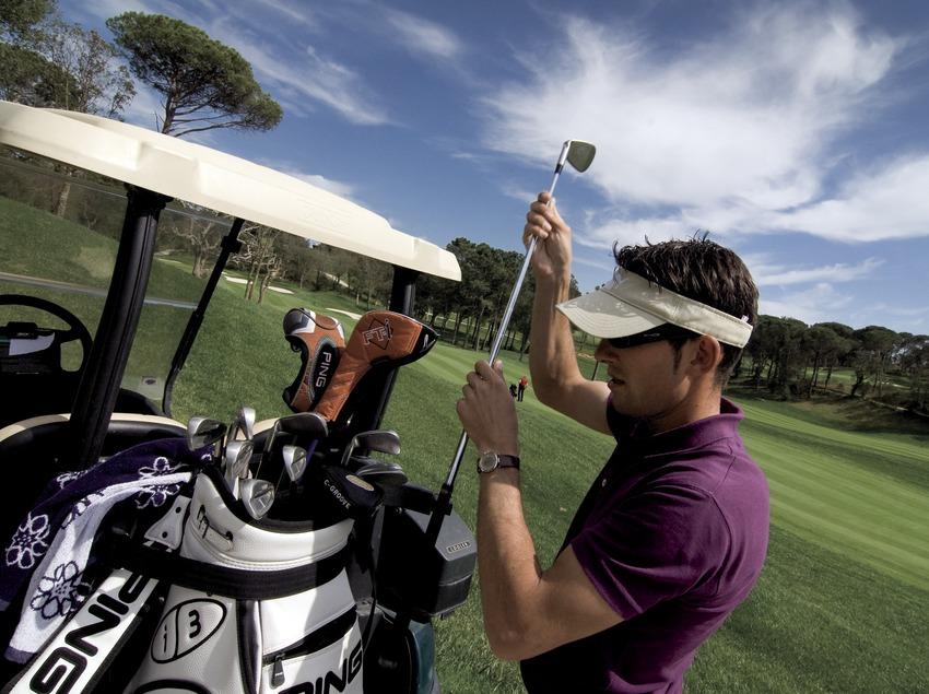 PGA Golf Catalunya. Un practicante cambia de palo en el buggy (Gemma Miralda)