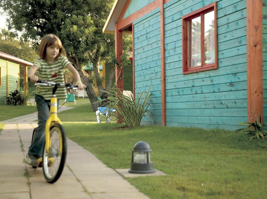 Niña con bicicleta entre los bungalows del camping Sangulí Resort (Cablepress)