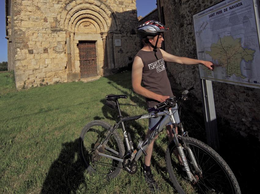 Consultant un plafó informatiu d'una ruta de BTT Salines-Bassegoda davant de l'església de Sant Pere de Navata (Cablepress)