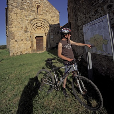 Consultando un plafón informativo de una ruta de BTT Salinas-Bassegoda ante la iglesia de Sant Pere de Navata