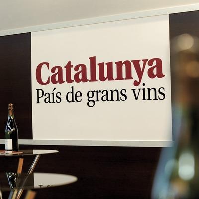 Rètol de Catalunya país de grans vins i tres ampolles de cava sobre les taules de vidre d'una recepció