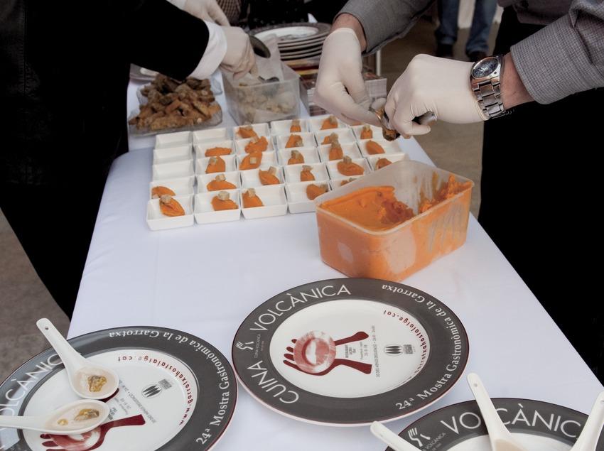 Exposition du collectif Cuina Volcànica et assiette avec logo, et cuisiniers au travail en arrière-plan (Marc Castellet)