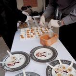 Mostra del col·lectiu Cuina Volcànica i un plat amb el logo, amb cuiners treballant al fons (Marc Castellet)