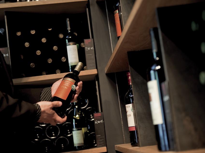 Винотека Torres. Магазин-винодельня. Посетитель с бутылкой красного вина Torres