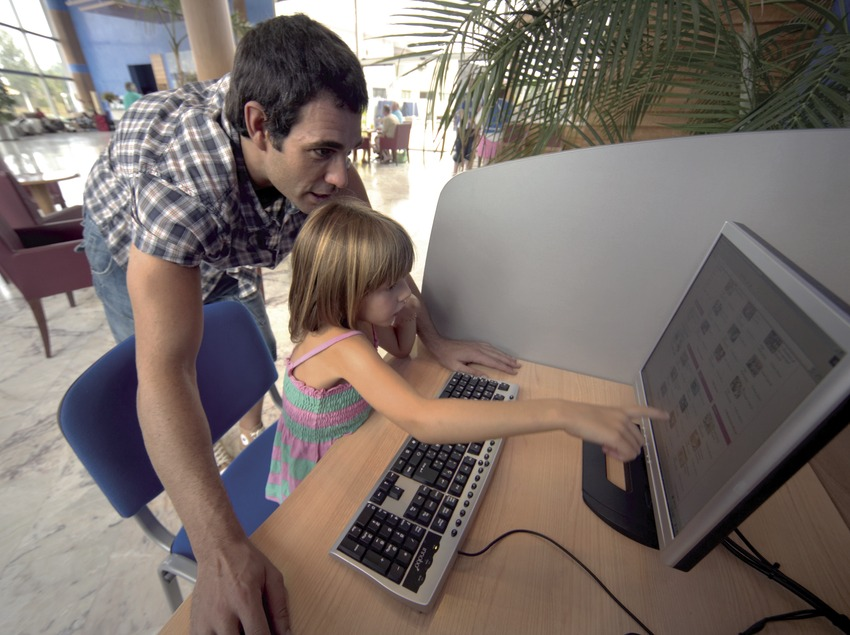 Father and daughter checking on the internet at the reception of the Hotel Sol Costa Daurada