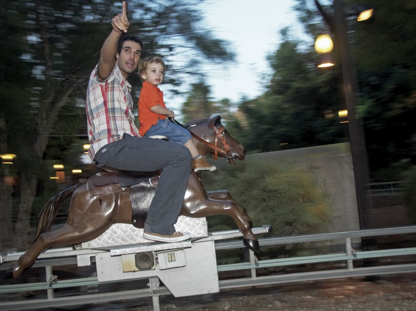 Father and son on one of the children's rides at PortAventura