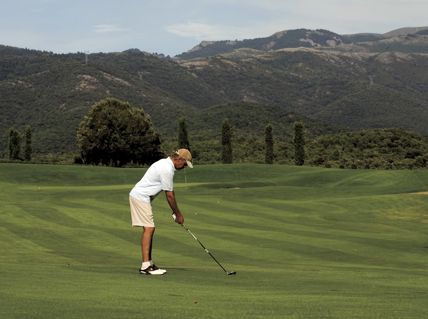 Club de Golf Montanyá. Practicante de golf en el campo con las montañas del Montseny al fondo (Gemma Miralda)