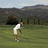 Club de Golf Montanyá. Un practicant de golf al camp amb les muntayes del Montseny al fons (Gemma Miralda)