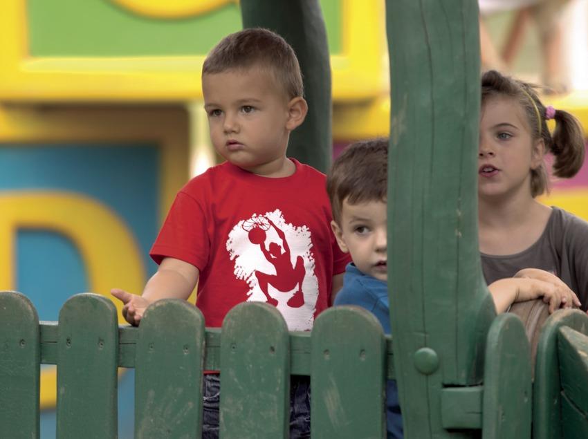 Niños detrás de una barrera de protección en el parque infantil Francesc Macià