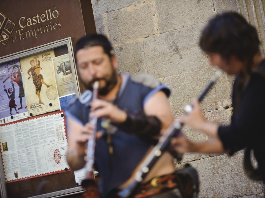 Festival Terra de Trobadors. Músics al carrer i logo del festival
