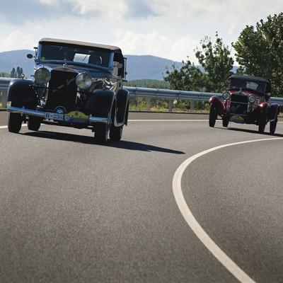 Dos dels cotxes participants a la XLVII Caravana de Cotxes Vetustos per una carretera secundària en direcció a Pals