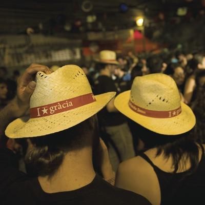 Dos personas llevan puesto el sombrero clásico repartido en la última edición de las Fiestas de Gràcia (Gemma Miralda)