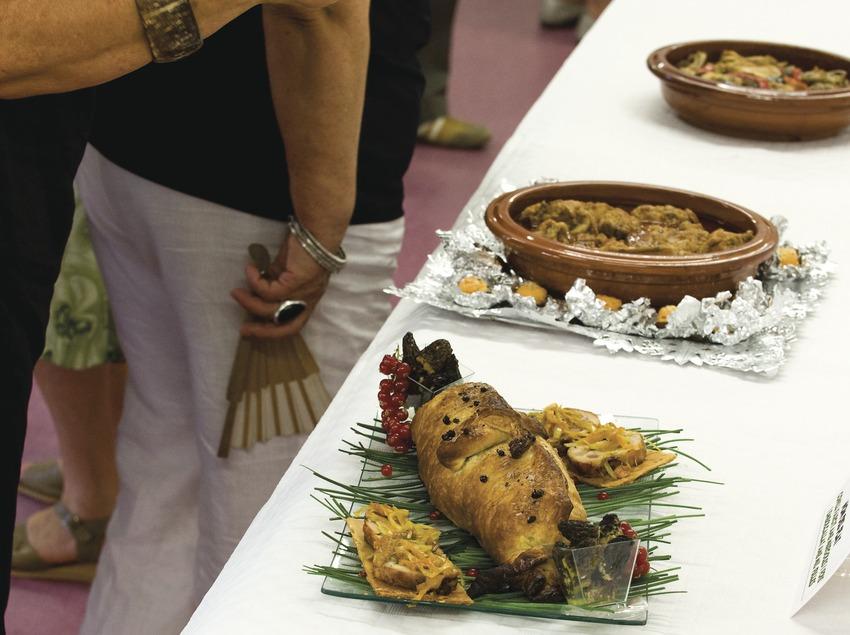 Public observant les différents plats présentés au concours de cuisine de Cunill. Fira de Sant Bartomeu ou foire aux melons