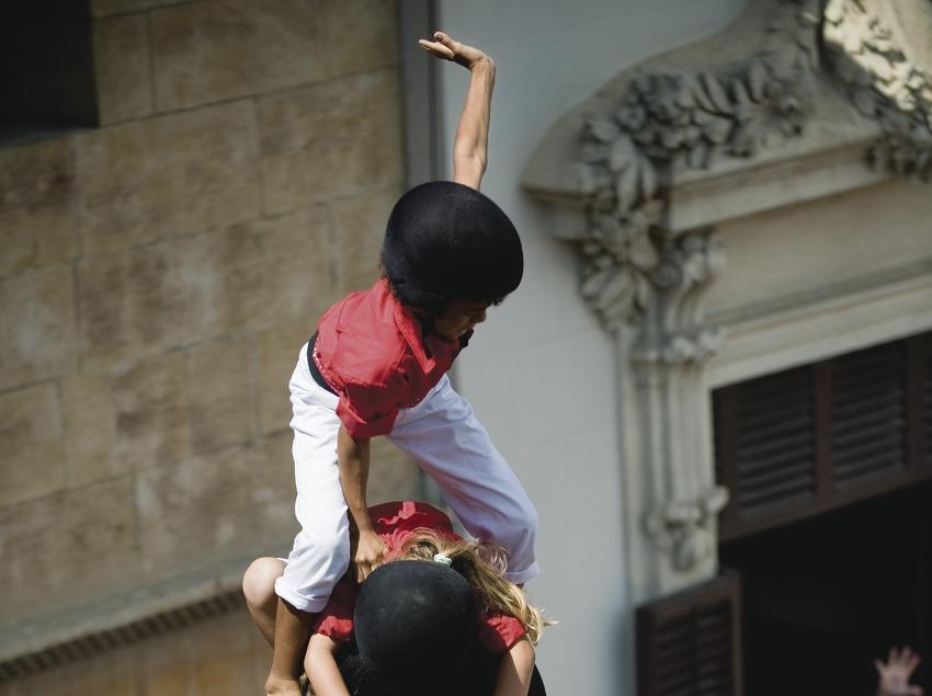 Gros plan sur le «Pom» (sommet) d'un «castell» (tour humaine) exécuté par la Colla Jove dels Xiquets de Valls avec la façade de l'hôtel de ville de Vilafranca en toile de fond. «Diada Castellera» (jour des tours humaines) de la fête de la Saint-Félix
