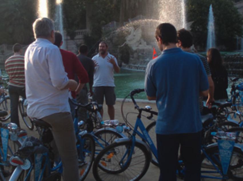 Grup de persones en bicicleta fent una ruta cultural amb guia per la ciutat de Barcelona.