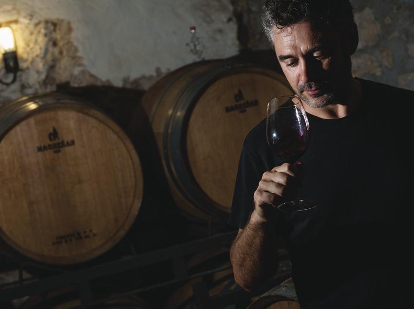 Jordi Llorens, propietari amb copa de vi al celler davant les barriques.