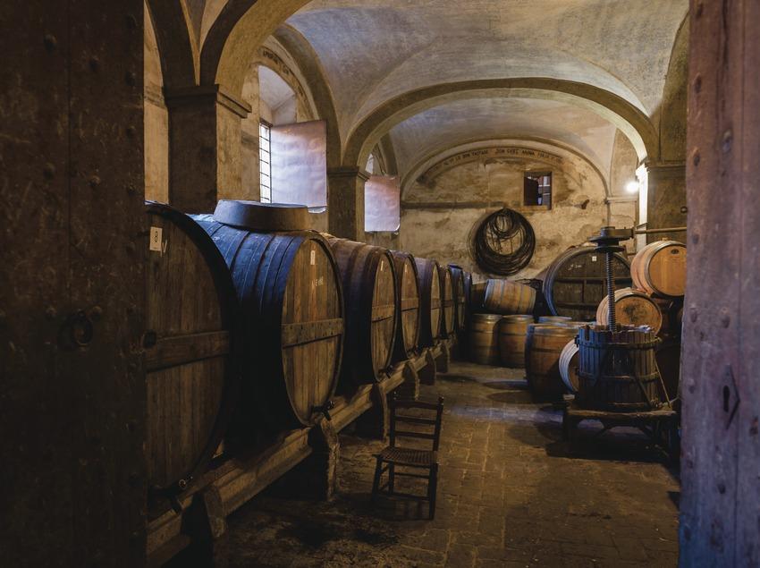 Celler Cal Pla, puerta de entrada y bodega con inscripciones históricas y alegóricas al vino en las paredes.