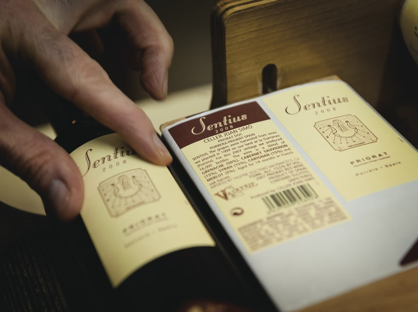 Celler Joan Simó, manos etiquetando botellas con el nombre de la marca.