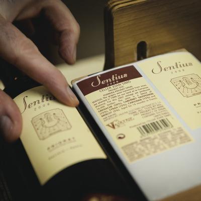 Celler Joan Simó, mans etiquetant ampolles amb el nom de la marca. (Marc Castellet)