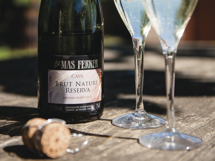 Caves el Mas Ferrer, copas de cava y botella en el jardín con la bodega de fondo.