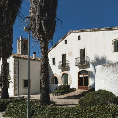 Coma Romà, façana de la masia amb campanar al fons.