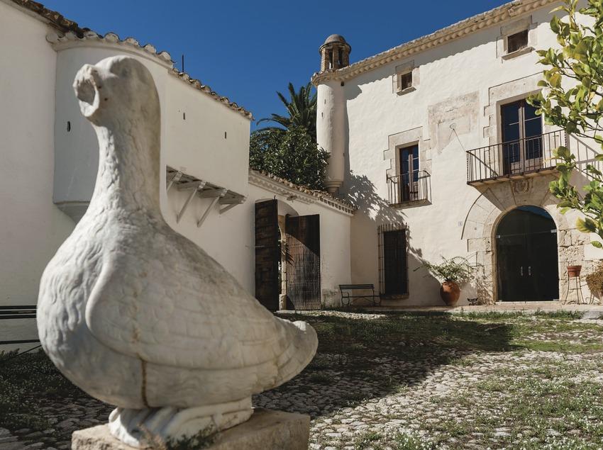 Can Ràfols dels Caus, entrada al patio de la masía con escultura en primer plano. (Marc Castellet)